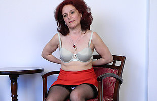 Horny mature slut masturbating in a chair