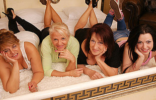Four old coupled with young lesbians making in foreign lands on bed